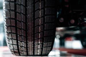 Imagen cercana de rueda de coche con neumático de caucho negro foto