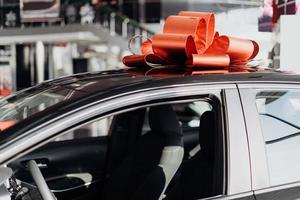 The new car is wrapped in a red bow. Beautiful gift concept photo