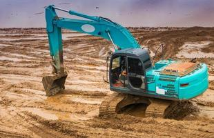Blackhoe is working on dredging the soil. photo