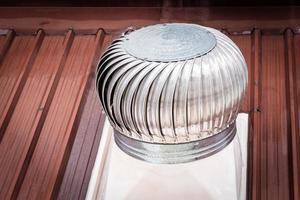 Chimenea de ventilación en el techo que depende del viento para girar. foto