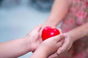 niño da corazón rojo a la abuela mayor. foto
