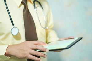El médico usa datos de búsqueda de tabletas en el hospital. foto
