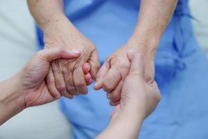 sosteniendo la mano paciente mujer mayor asiática con amor. foto