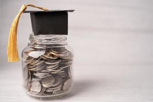 Sombrero de brecha de graduación en monedas dinero en jar foto