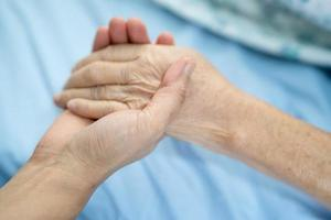 Doctor holding touching hands Asian senior woman patient with love photo