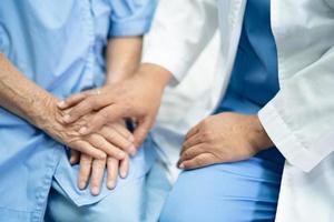 doctor, conmovedor, manos, asiático, mayor, dama, mujer, paciente, con, amor foto