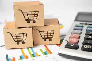Shopping cart logo on box with calculator on graph background. photo