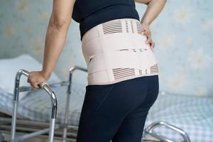 Paciente dama asiática vistiendo soporte para el dolor de espalda foto