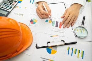 Engineer working project accounting with graph photo