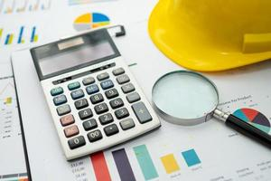 calculadora en gráfico con casco de construcción foto