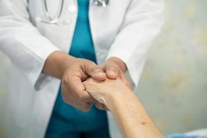 Doctor holding touching hands Asian senior woman patient with love, photo