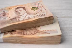 Stack of Thai baht banknotes on wooden background, photo