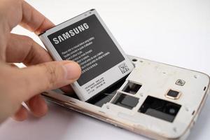 Bangkok, Tailandia, 01 de julio de 2020: técnico reparando una batería Samsung en un teléfono inteligente foto