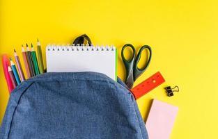 Mochila escolar con material de oficina sobre fondo amarillo foto