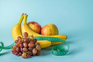 Ripe fruits and measuring tape on a blue background photo
