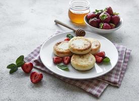 panqueques de requesón en plato de cerámica con fresa fresca. foto