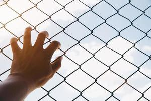 Hope concept,unhappy man hand sad hopeless at fence prison in jail, photo