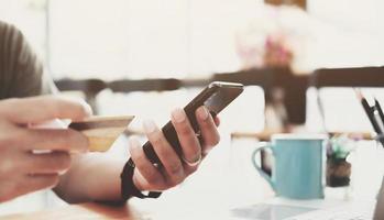 pago en línea, manos del hombre sosteniendo un teléfono inteligente y con tarjeta de crédito foto
