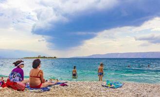 Turistas en la playa de novi vinodolski, croacia foto