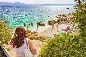 Tourists go to turquoise water beach seascape Novi Vinodolski, Croatia photo