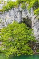 Turistas en una cueva en el parque nacional de los lagos de Plitvice, Croacia foto