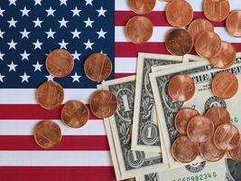 billetes de dólar y monedas y bandera de los estados unidos foto