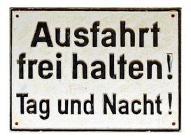 signo alemán aislado sobre blanco. Salga, manténgase despejado de día y de noche. foto