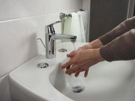 Unrecognisable man washing hands photo