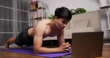 Man Using a Laptop and Doing Planks video