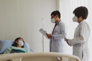 Médico y estudiante de medicina visitan al paciente en la sala del hospital. foto
