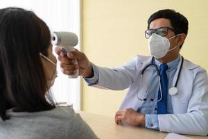 Médico con termómetro digital para medir la temperatura del paciente. foto