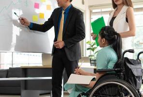 Mujer discapacitada sentarse en silla de ruedas discutir el proyecto con un colega foto
