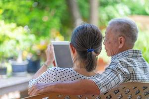 senior asian couple using tablet to read social media together at home photo