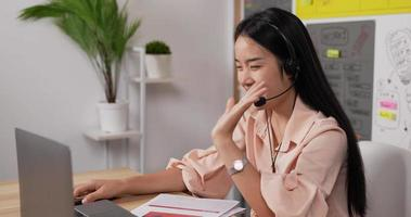 mujer con auriculares usando laptop y hablando video