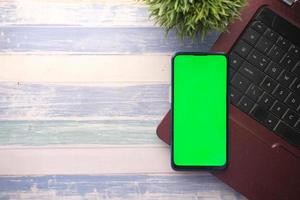 smart phone with empty screen, laptop on wooden background photo