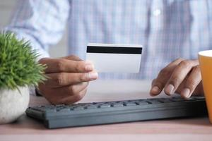 man hands holding credit card and using laptop shopping online photo