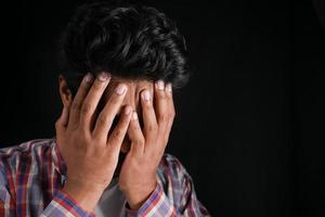 Close up of sad man covering face with hand. photo
