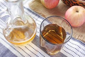 Vinagre de manzana en botella de vidrio con manzana verde fresca en la mesa foto