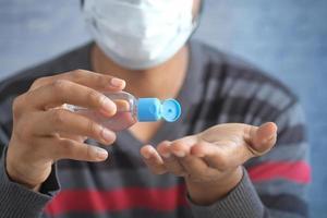 man in face mask using sanitizer liquid for preventing corona virus photo