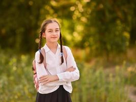 Young schoolgirl with backpack. Outdoor autumn park. Back to school photo