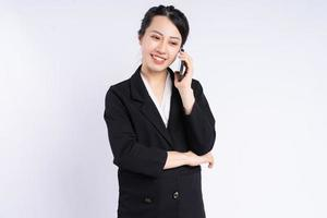 Joven empresaria asiática con smartphone sobre fondo blanco. foto