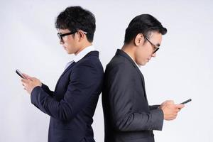 Two Asian business men leaning against each other photo