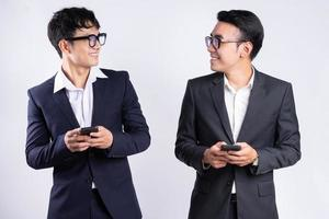 Two Asian businessmen using smartphone on white background photo
