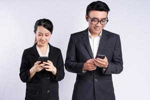 Asian businessman and businesswoman using smartphone photo