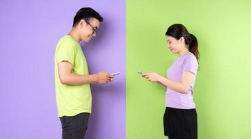 Young Asian couple using smartphone, long distance love concept photo