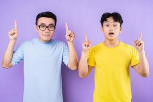 Two Asian brothers posing on purple background photo