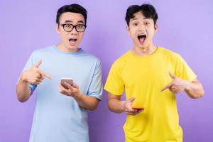 Two Asian brothers using cell phones on purple background photo