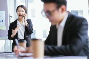 Portrait of Asian businesswoman calling her partner photo