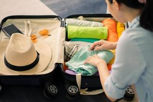 Asian woman arranges clothes in suitcase to prepare for travel photo