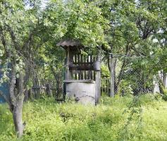 Viejo pozo con balde de hierro en cadena forjada larga foto
